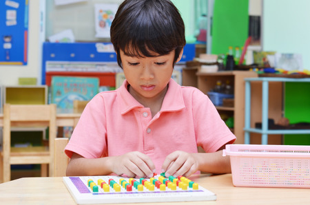 educational materials: Little boy study color of pin made of montessori educational materials