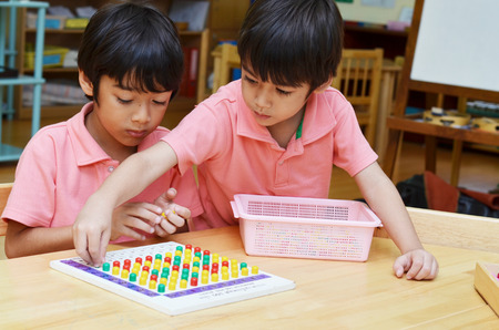 Little boys study color of pin made of montessori educational materials