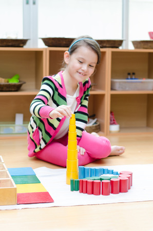 materials: Little girl hand building tower made of montessori educational materials   Stock Photo