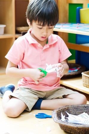 Kleine jongen het snijden van papier van montessori onderwijs