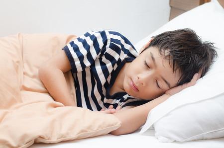teen boy face: Little boy sleeping on bed Stock Photo