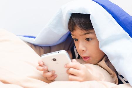 Little boy using mobile under blanket photo