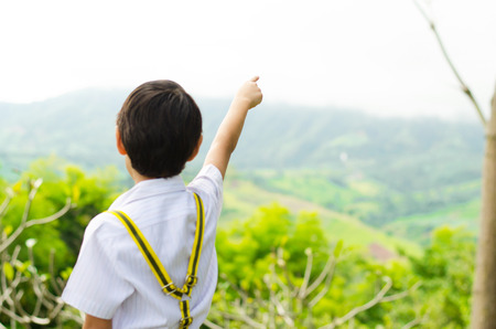 Little boy pointing his finger to the sky on the hill photo