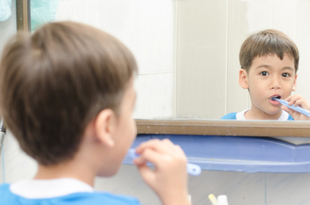 Little Boy Brushing Teeth looking on mirror Stock Photo - 31955305