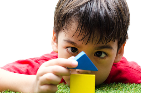 little boy building a small house with colorful wooden blocks Stock Photo