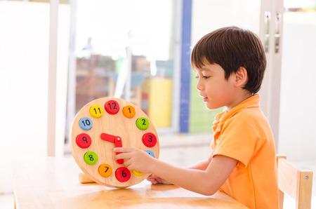 Jongetje leertijd met klok speeltje van montessori educatief materiaal