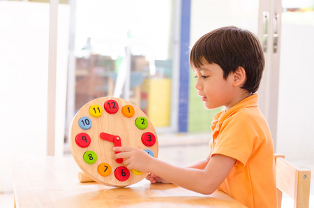 preteen boys: Little boy learning time with clock toy of montessori educational materials Stock Photo