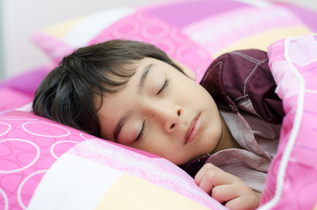 Little boy sleeping in bed on white background