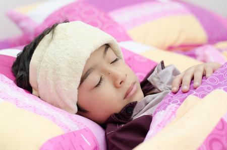 Jongetje heeft koorts met handdoek op hoofd