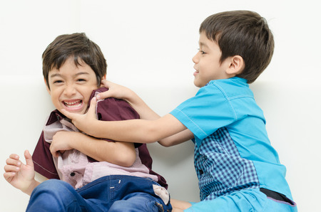 Little sibling boy  fighting on sofa Stock Photo
