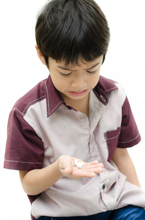 Little boy doesn want to take medicine pill on white background photo