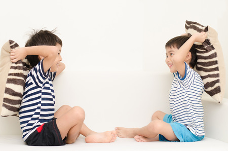 Little sibling boy playing pillow fighting on sofa photo