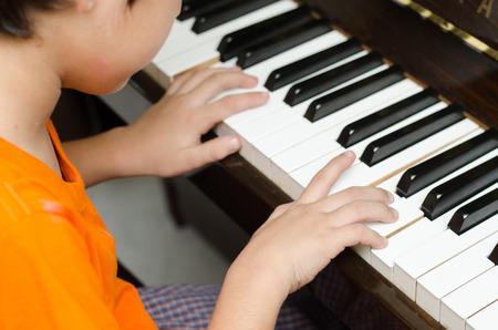 little boy playing piano 스톡 콘텐츠