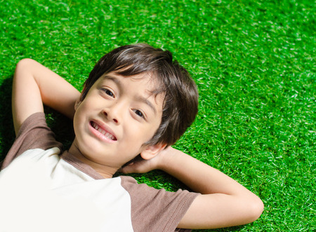 Little boy lay down on green grass
