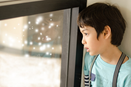 look out: Little boy looking at snow outside of window