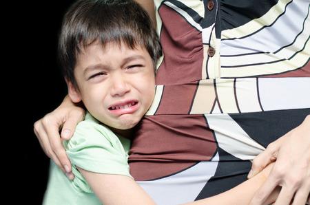 Littleboy huilen met zijn moeder een zwarte achtergrond Stockfoto