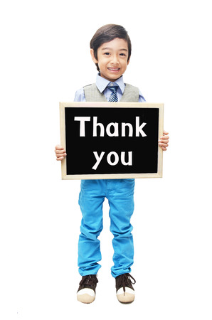 Little boy showing blackboard word thank you on white background