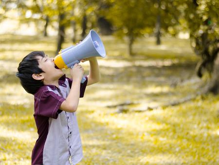 Little boy hold megaphone in the park Standard-Bild