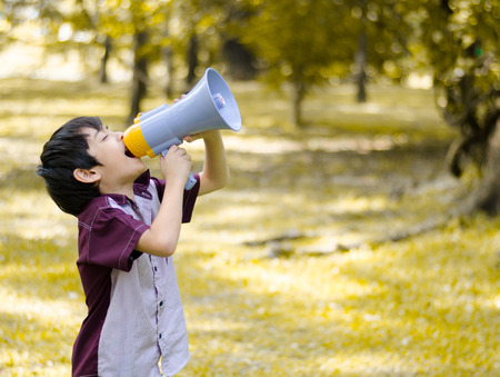 Little boy hold megaphone in the park Archivio Fotografico