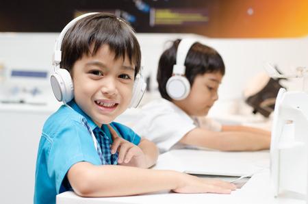 Kleine jongen met hoofdtelefoon in de klas Stockfoto