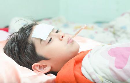 ni�os enfermos: Muchacho enfermo peque�o con la temperatura en la boca