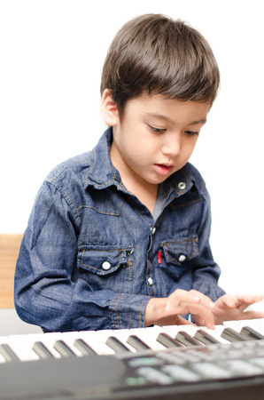 Little boy playing keyboard on white backgroud photo