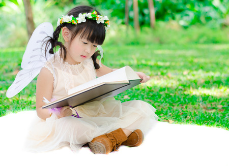 Little girl reading book in the park vintage style photo