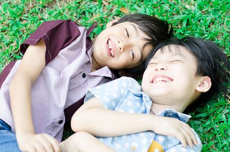 reir: Amigos del niño pequeño reír juntos en el parque Foto de archivo