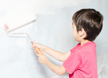 wall paintings: Little boy painting wall white color at home Stock Photo