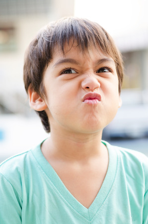 Little boy with angry grumpy face photo