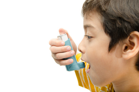 Little boy using Asthma inhaler for breathing on white background photo