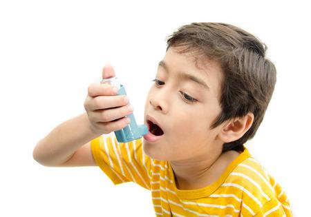 Little boy using Asthma inhaler for breathing on white background