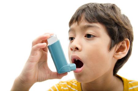 aparato respiratorio: El ni�o peque�o usando asma inhalador para respirar en el fondo blanco