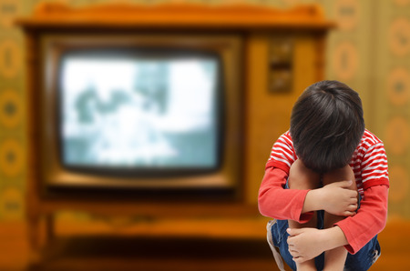 upset: Kid sitting with sadness and sick from tv addict need love from parent  black and white Stock Photo