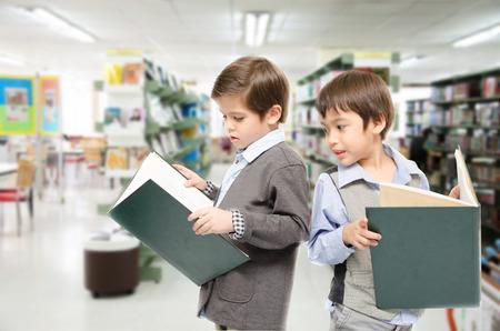 library: Los ni�os peque�os la lectura de libros en la biblioteca Foto de archivo
