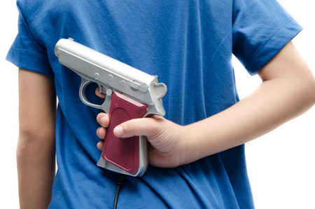 holding gun: Little boy hinding gun behind his back