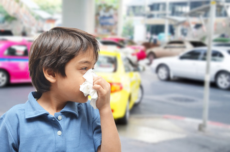 Little boy sneezing cause allergic on the road