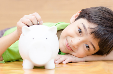 white piggy bank: Little boy saving money in piggy bank Stock Photo