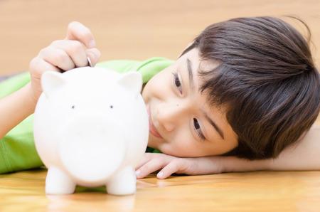 돼지 저금통에 돈을 절약 어린 소년
