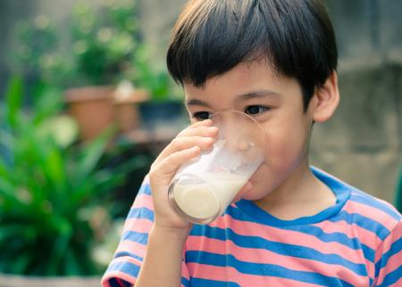 Littl boy drinking milk in the park vintage color style Standard-Bild