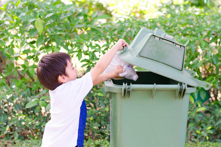 Little boy  hand taking garbage in to the bin Stock Photo