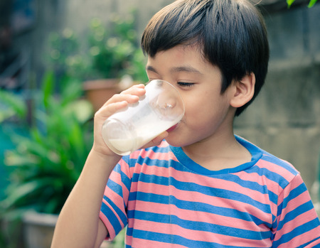 energy drink: Littl boy drinking milk in the park vintage style
