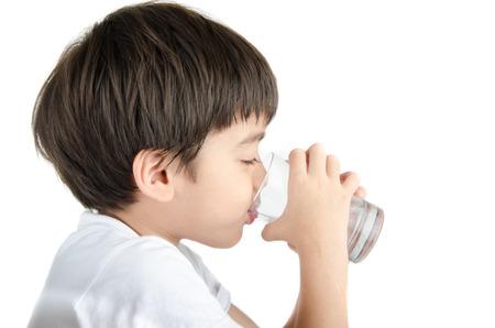 vasos de agua: pequeño muchacho asiático bebe el agua de un vaso