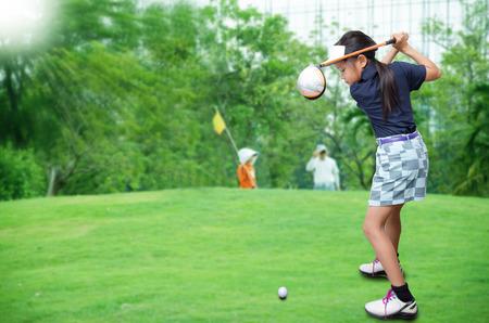 Kleines asiatisches Mädchen Golf spielen