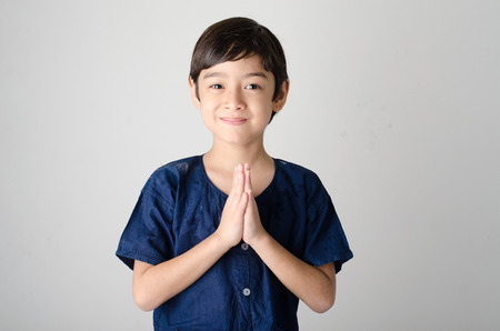 orando: El ni�o peque�o asi�tica orando en traje tailand�s aislar sobre fondo blanco Foto de archivo