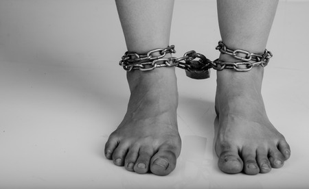 Woman feet was tied by chain isolate on white background photo