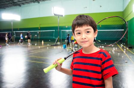 Kleine jongen die badminton racket in training klasse in de sportschool