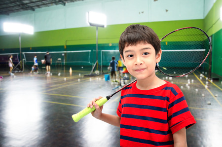 Little boy taking badminton racket in training class at the gym