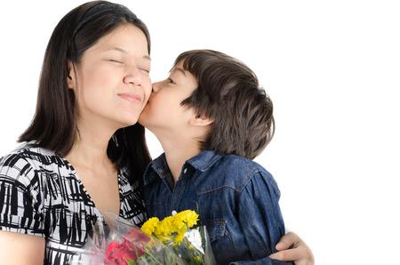 Kleine jongen kuste zijn moeder met bloem op een witte achtergrond Stockfoto