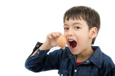 Little boy holding egg in hand mouth wide healthy on white background
